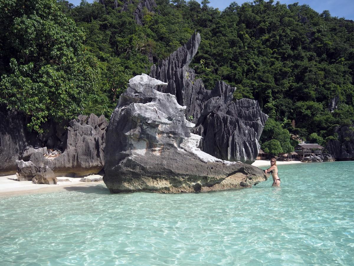 Nastya near the rocks on Banul beach, Philippines - Travelblogstories